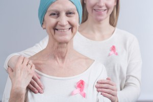 60511163 - woman after breast cancer is hugged by her close female person . both woman have pink ribbons